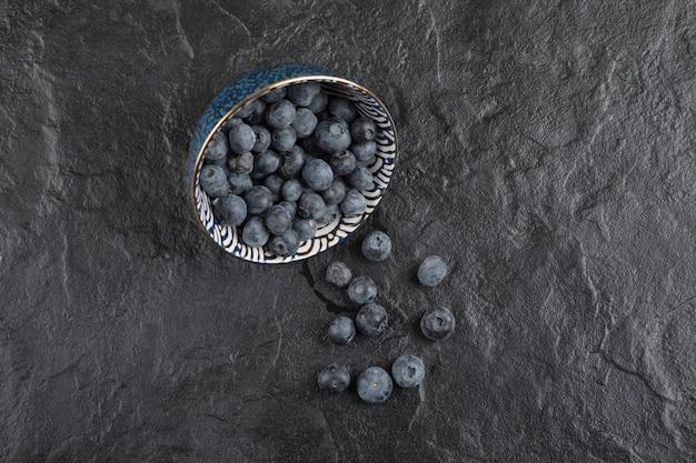 Ciotola in ceramica di deliziosi mirtilli freschi su superficie nera