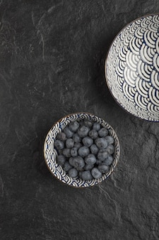 Ceramic bowl of delicious fresh blueberries on black surface