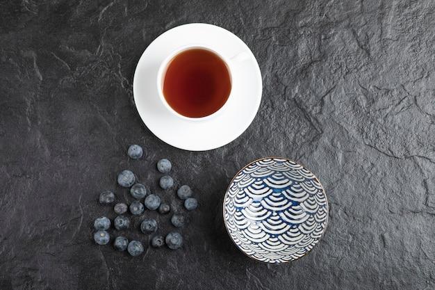 Ciotola in ceramica di deliziosi mirtilli freschi e tazza di tè su superficie nera