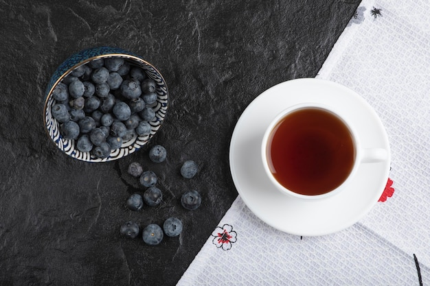 Ceramic bowl of delicious fresh blueberries and cup of tea on black surface