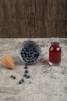 Ceramic bowl of delicious fresh blueberries and glass of juice