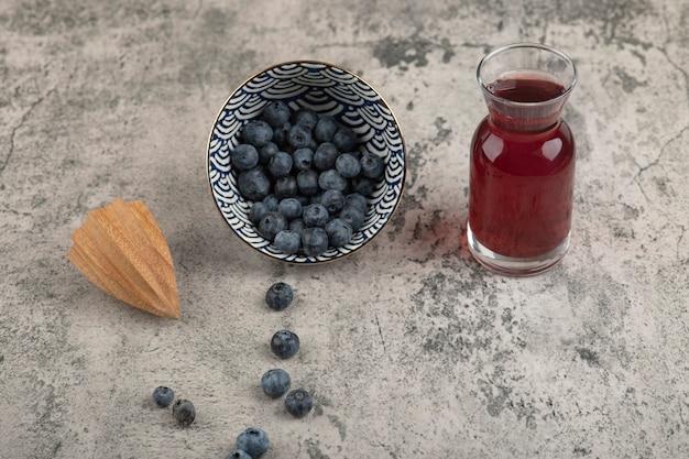 Ciotola in ceramica di deliziosi mirtilli freschi e bicchiere di succo