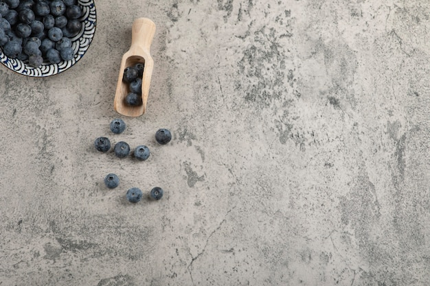 Ceramic bowl of delicious fresh blueberries on marble surface