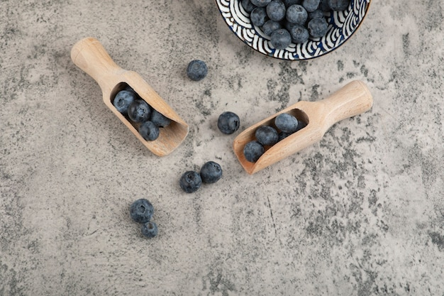 Ceramic bowl of delicious fresh blueberries with wooden spoon