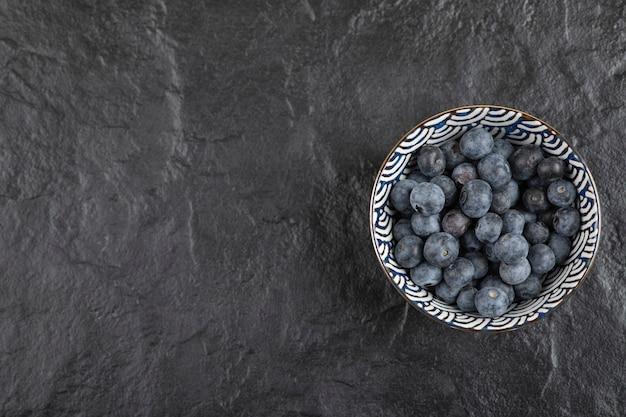 Ciotola in ceramica di deliziosi mirtilli maturi su superficie nera