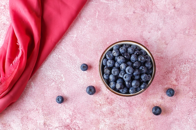 Ceramic bowl of delicious ripe blueberries on marble surface