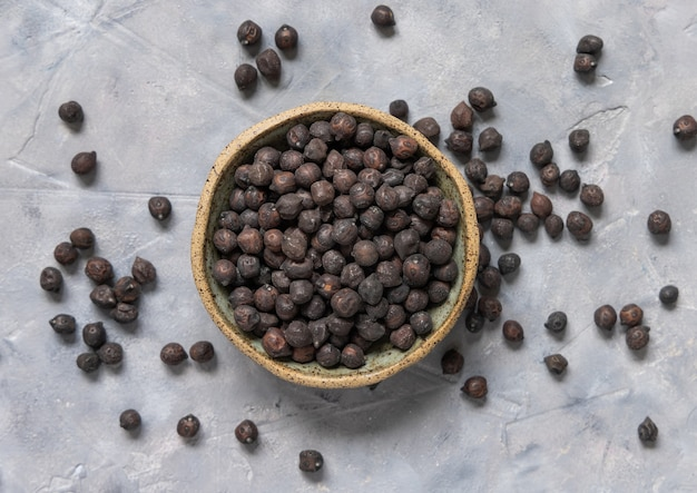 Ceramic bowl of dry black chickpea from apulia and basilicata in italy on grey table top view