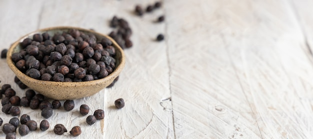 Ceramic bowl of dry black chickpea from apulia and basilicata in italy on grey table with copy space, closeup