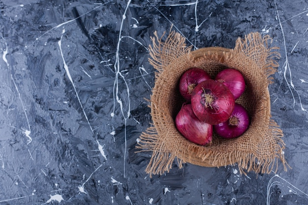 Ceramic bowl of fresh red onions on blue background.