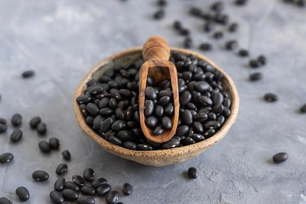 灰色のテーブルに木製のスクープが付いた乾燥黒豆でいっぱいのセラミックボウルは、ネガティブスペースでクローズアップします。健康的な食事と菜食主義の概念。伝統的なラテンアメリカのいとこ成分