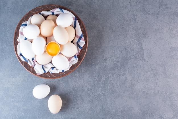 Ceramic bowl full of organic eggs on stone table.