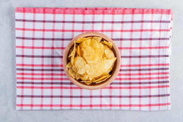 돌 배경에 맛있는 바삭바삭한 칩의 세라믹 그릇.