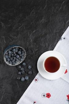 黒い表面においしい新鮮なブルーベリーとお茶のセラミックボウル