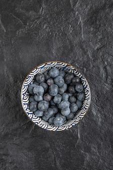 黒い表面においしい新鮮なブルーベリーのセラミックボウル
