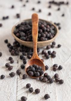 灰色のテーブルとコピースペース、クローズアップとスプーンでイタリアのプーリア州とバジリカータ州からの乾燥した黒いひよこ豆のセラミックボウル