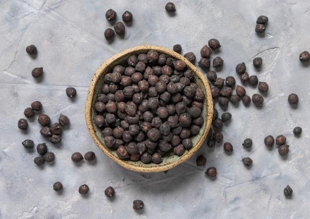 灰色のテーブルトップビューでイタリアのプーリア州とバジリカータ州からの乾燥した黒いひよこ豆のセラミックボウル