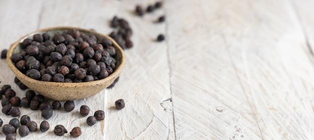 コピースペース、クローズアップと灰色のテーブルにイタリアのプーリア州とバジリカータ州からの乾燥した黒いひよこ豆のセラミックボウル
