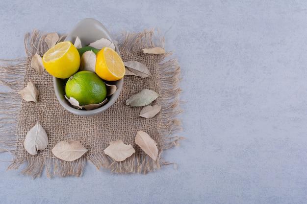 石のテーブルに新鮮なジューシーなレモンのセラミックボウル。