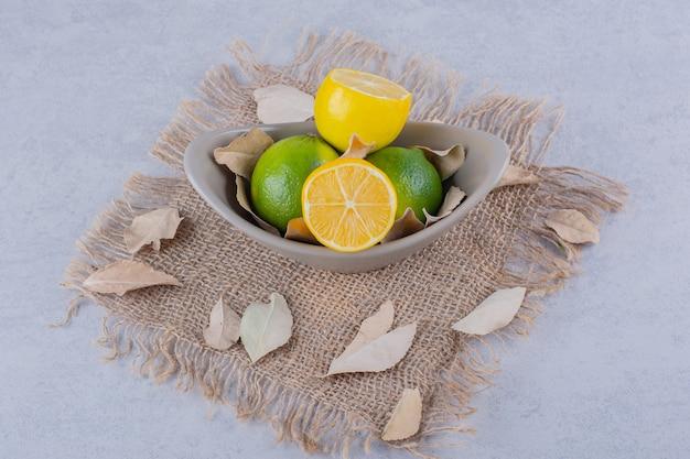 Керамическая миска свежих сочных лимонов на каменном столе.
