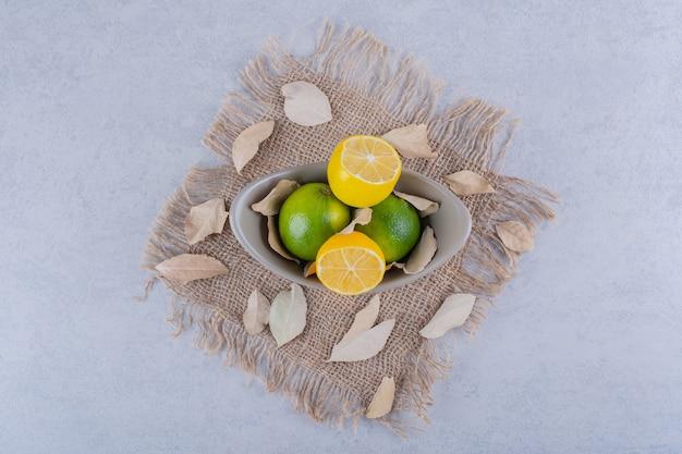 Керамическая миска свежих сочных лимонов на камне.