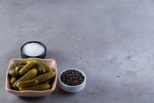 きゅうりのピクルスと調味料のセラミックボウルを石のテーブルに。
