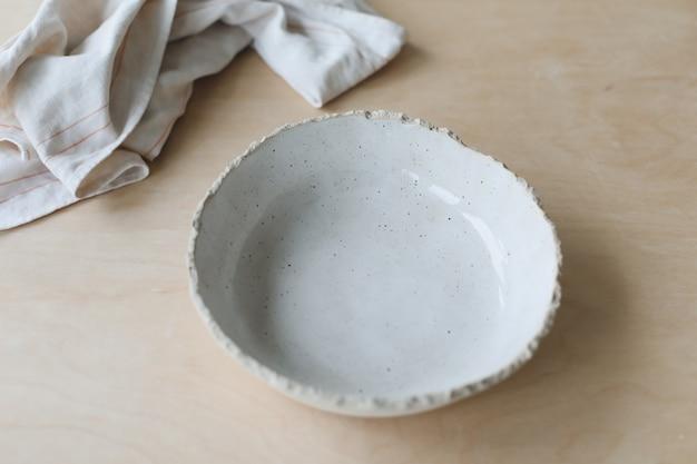 Керамическая миска на деревянном столе, вид керамической посуды и керамики ручной работы