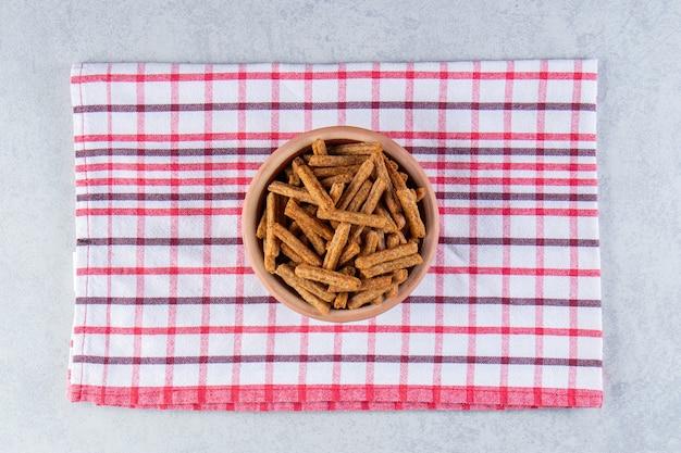 Ceramic bowl of tasty crunchy crackers on stone background.