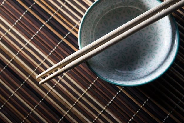 Ceramic bowl with chopsticks on bamboo background
