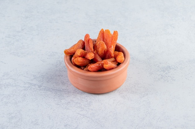 Ciotola in ceramica con deliziosi frutti secchi su sfondo di pietra.