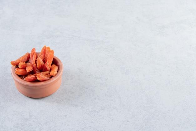 Ciotola in ceramica con deliziosa frutta secca su pietra.