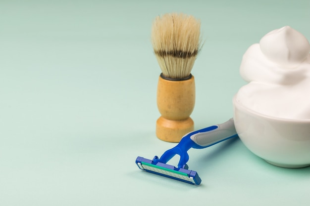 Ceramic bowl with lots of shaving foam, shaving brush and razor on a blue surface. set for care of a man's face.