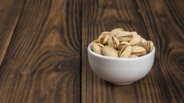 木製のテーブルにピスタチオとセラミックボウル