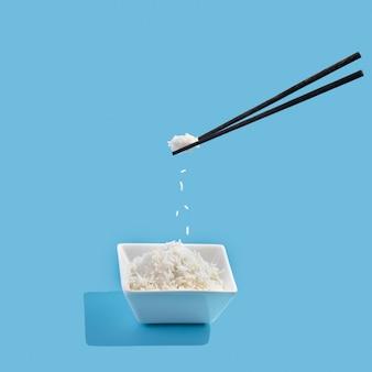 파란색 배경에 쌀과 공중 부양 젓가락이 있는 세라믹 그릇.