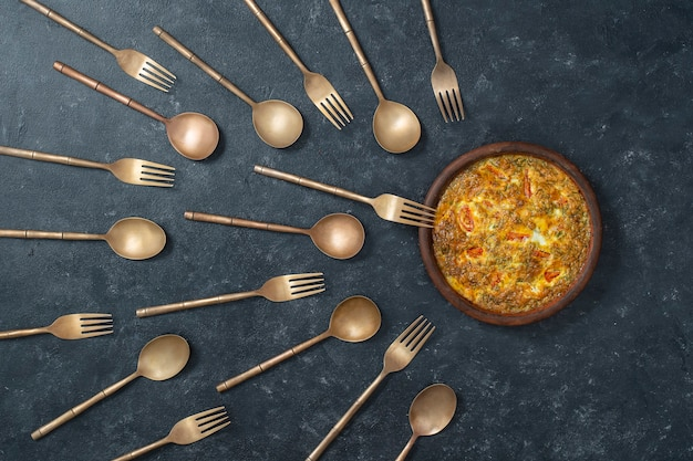 Ceramic bowl with vegetable frittata and brass forks and spoons look like sperm competition.