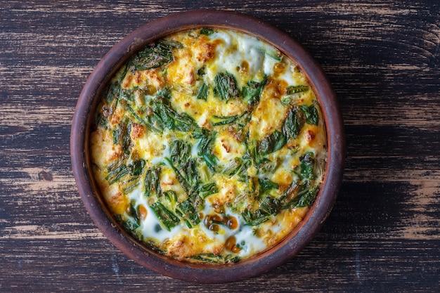 Керамическая миска с овощной фриттатой, простое вегетарианское блюдо. фриттата с яйцом, перцем, луком, сыром и зелеными листьями дикого чеснока на столе, крупным планом. здоровый яичный омлет