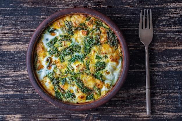 野菜のフリッタータ、シンプルなベジタリアン料理のセラミックボウル。卵、コショウ、タマネギ、チーズ、緑の野生のニンニクの葉をテーブルに置いたフリッタータをクローズアップします。ヘルシーエッグオムレツ