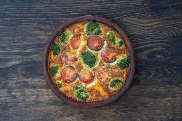 Керамическая миска с овощной фриттатой, простое вегетарианское блюдо. фриттата с яйцом, помидорами, перцем, луком, брокколи и сыром на деревянном столе, крупным планом. яичный омлет по-итальянски