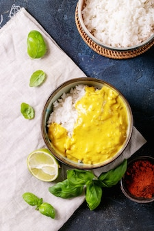 Ceramic bowl of yellow curry served with basil and limes