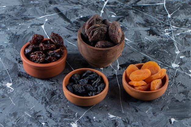 Ceramic bowls of tasty dried fruits on marble surface.