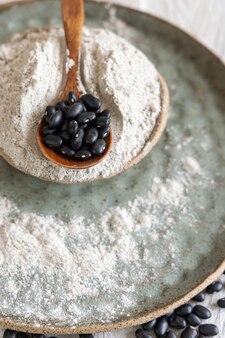 黒豆粉と木のスプーンのクローズアップと乾燥豆のセラミックボウル。健康的な食事と菜食主義の概念。伝統的なラテンアメリカのいとこ成分
