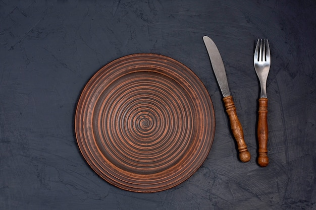 Керамическая тарелка коричневого цвета с вилкой и ножом на черном столе