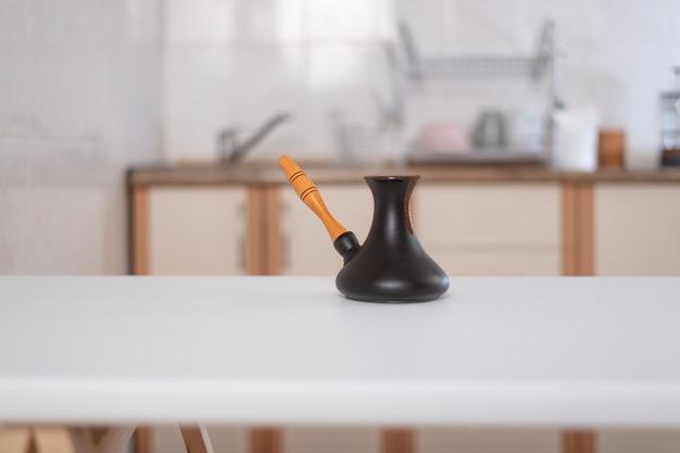 Керамический кофейник турки турецкий на предпосылке кухни. рецепт приготовления кофе.