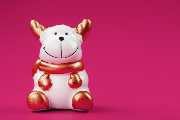 분홍색 배경에 세라믹 크리스마스 소 황소 장난감