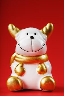 빨간색 배경에 세라믹 크리스마스 암소 황소 장난감.