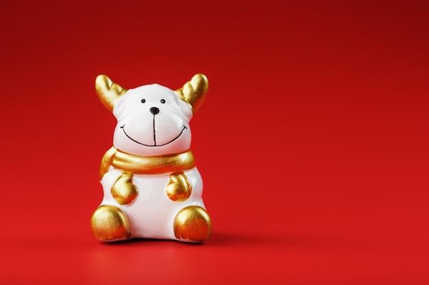 Керамическая рождественская игрушка корова бык на красном фоне
