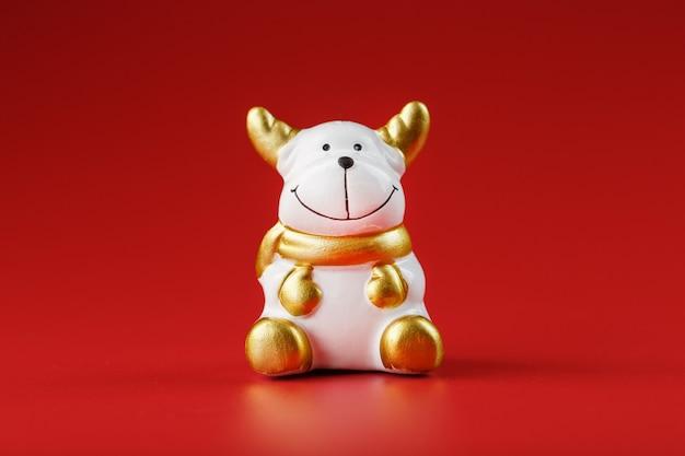 빨간 벽에 세라믹 크리스마스 암소 황소 장난감. 새해의 상징. 분리