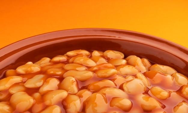 브라운에 토마토 소스에 구운 콩 세라믹 클레이 플레이트를 닫습니다.