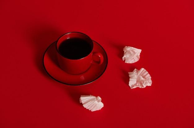 赤い受け皿にコーヒーが入ったセラミックコーヒーカップ、チョコレートプラリネのしわくちゃの紙のラッパーの横にあり、テキスト用のスペースがある赤い表面に分離されています