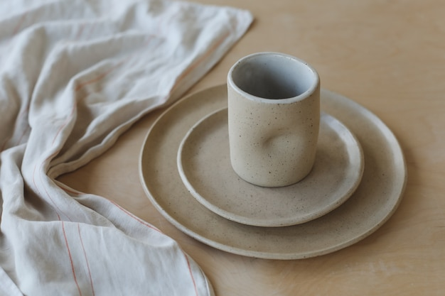 木製のテーブルトップビューのセラミックカップとプレート手作りのセラミック食器のミニマリストセットと...