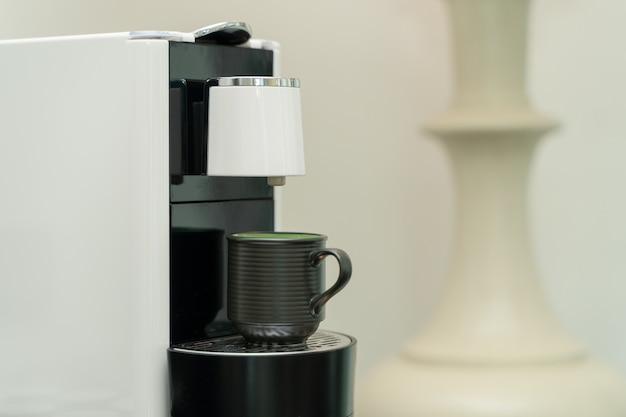Ceramic cup of coffee on the coffee machine. coffee capsule machine maker.